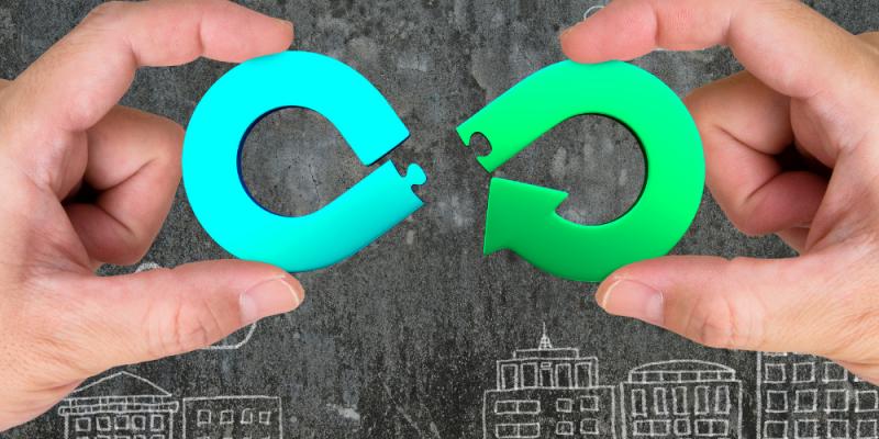 Duas mãos segurando dois pedaços do símbolo do infinito, sendo um deles azul e outro verde, no fundo cinza, com desenhos em branco de prédios.