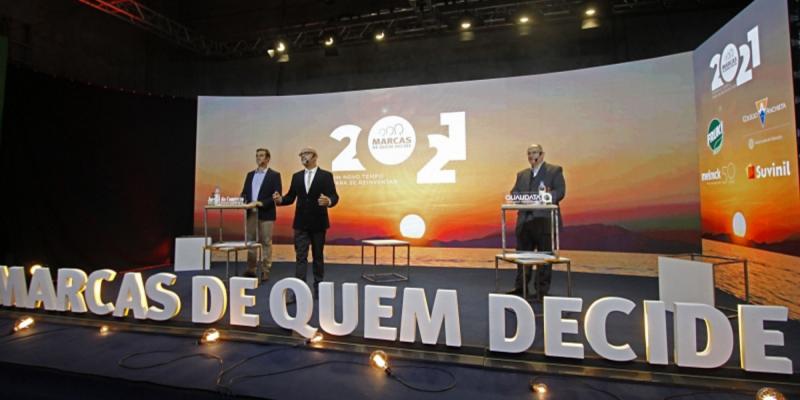 Imagem de um palco, com um letreiro escrito Marcas de Quem Decide 2021 com três homens vestindo terno, um deles em um púlpito