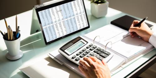 Pessoa com calculadora nas mãos e uma caneta na outra, tablet em cima da mesa e folhas